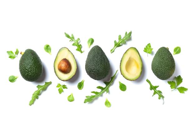 Кусочки свежих авокадо с зелеными листьями, изолированные на белом фоне. плоская планировка.