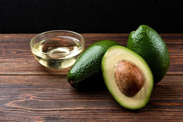 Свежие авокадо с маслом на деревянном столе