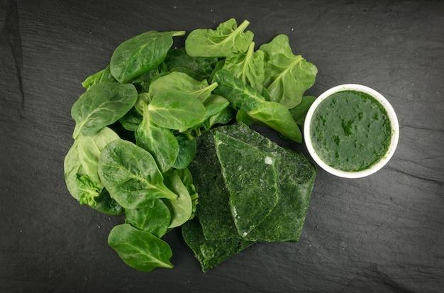 新鮮なほうれん草の葉と冷凍ほうれん草。ホワイトボウルの冷凍ほうれん草。葉物野菜の上面図