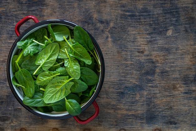Foglie di spinaci freschi in una ciotola su un tavolo in legno rustico. copia spazio