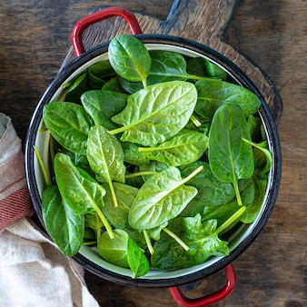 Fresh baby spinach leaves in a bowl on a rustic wooden table. square