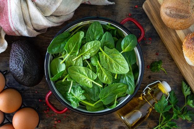 新鮮なほうれん草の葉をボウルに入れ、卵を木製のテーブルに置きます。上面図。コピースペース