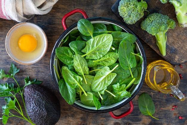 新鮮なほうれん草の葉をボウルに入れ、卵を木製のテーブルに置きます。上面図。