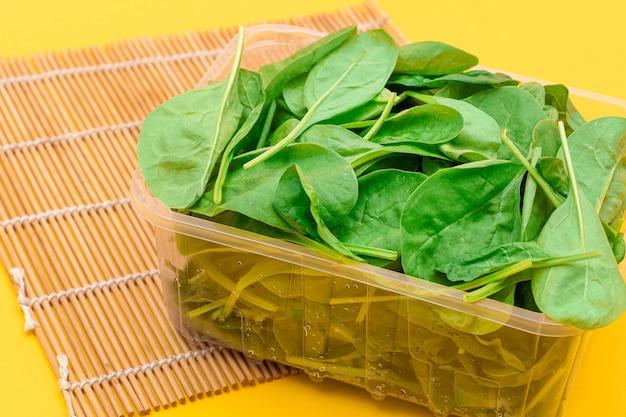 Свежие молодые листья шпината в прозрачном пластиковом пакете на желтом фоне