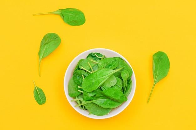Свежие молодые листья шпината в белой миске на желтом фоне