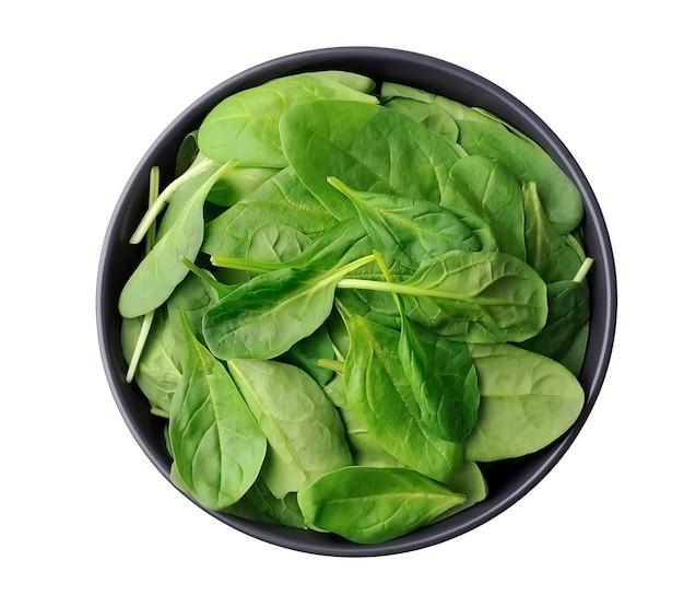 Свежие листья шпината ребенка на тарелке изолированные