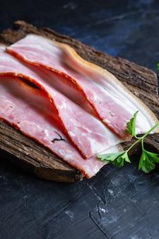 Fresh bacon thin strip slice fatty meat and lard piece