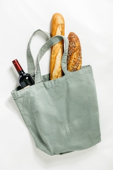 Fresh baguette and bottle of wine in cotton bag. bakery products. friendly packaging.