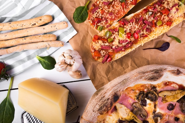 Fresh baguette pizza; cheese block; grater; bread sticks; garlic white pizza on table