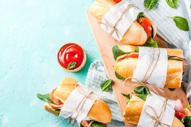 Fresh baguette sandwich with bacon cheese tomatoes and spinach light blue background
