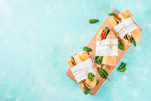 Fresh baguette sandwich with bacon, cheese, tomatoes and spinach, light blue   top view