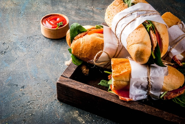 Fresh baguette sandwich with bacon, cheese, tomatoes and spinach