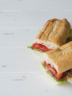 Fresh baguette sandwich with meat, sliced cheese, tomatoes and fresh lettuce