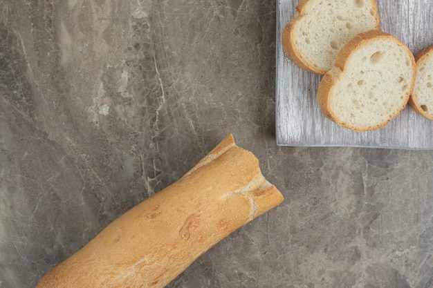 Fresh baguette slices on marble background. high quality photo