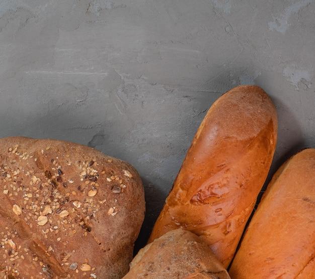 テキスト用の空きスペースがある灰色の背景に焼きたてのバゲットとパン。