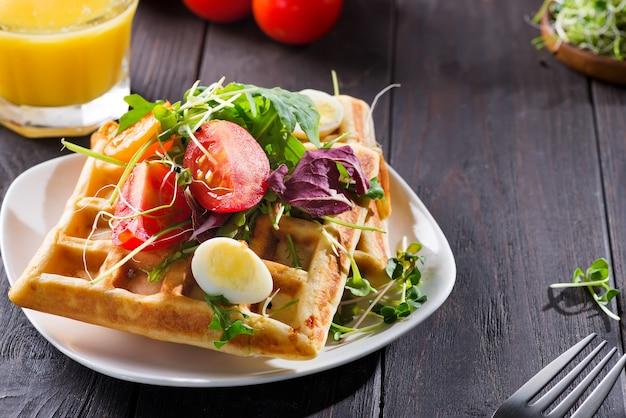 Свежие запеченные бельгийские вафли с рукколой, помидорами и авокадо на тарелке