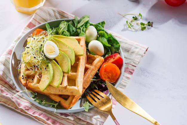 Свежие запеченные бельгийские вафли со шпинатом, яйцом, помидорами и авокадо на синей тарелке