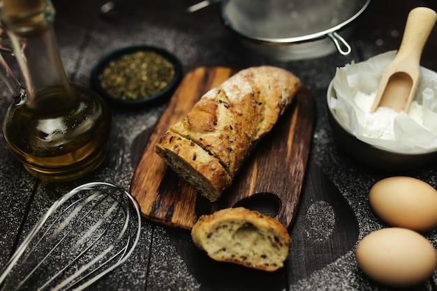 Свежий испеченный хлеб и ингредиенты для выпечки на столе. фото высокого качества