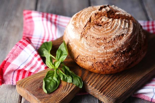 Свежеиспеченный хлеб и свежий базилик на разделочной доске, на деревянном столе