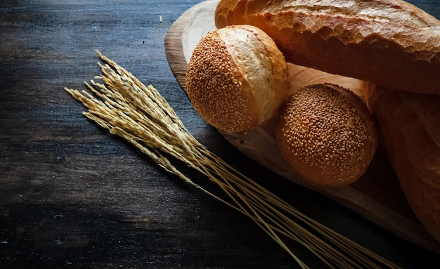 Fresh baked bread and baguette on wooden background