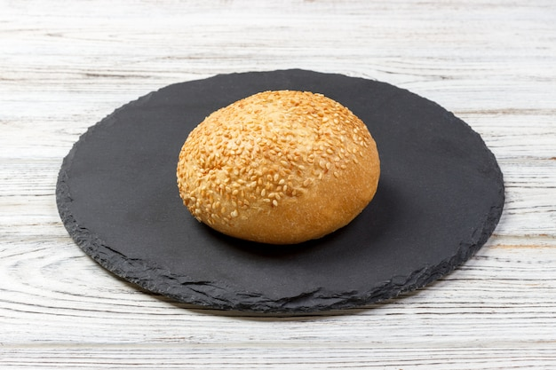 Fresh baked bread or bun with sesame and sunflower seeds on slate board