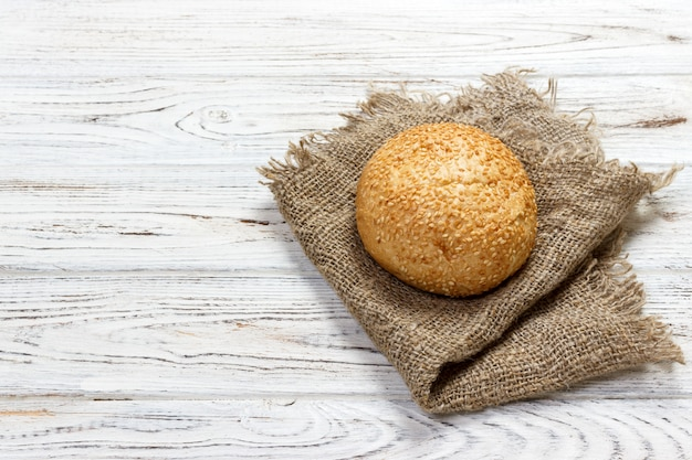 Fresh baked bread or bun with sesame and sunflower seeds on wooden table