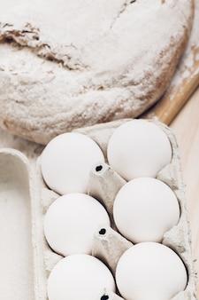 木製のテーブルに焼きたてのパン、小麦粉、卵。柔らかな光