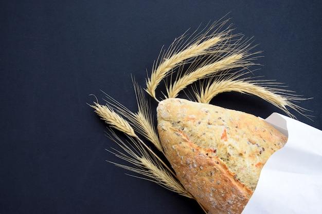 Свежеиспеченный хлебец с колосками пшеницы на черной доске. концепция пекарни или кухни. плоский вид сверху с копией пространства.