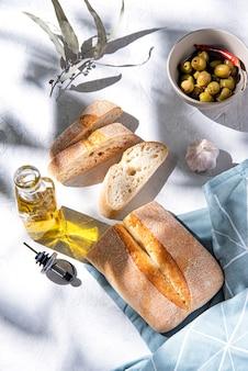 朝の陽光の下でオリーブとオイルをテーブルに焼きたてのパン。上面図