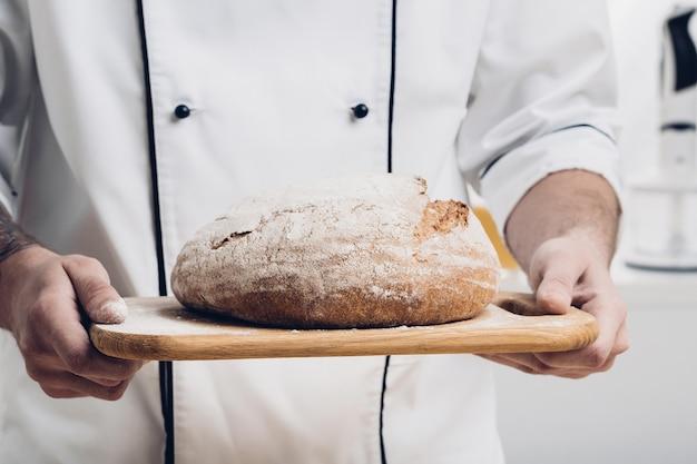 빵 굽는 사람의 손에 있는 나무 판자에 갓 구운 빵. 부드러운 빛
