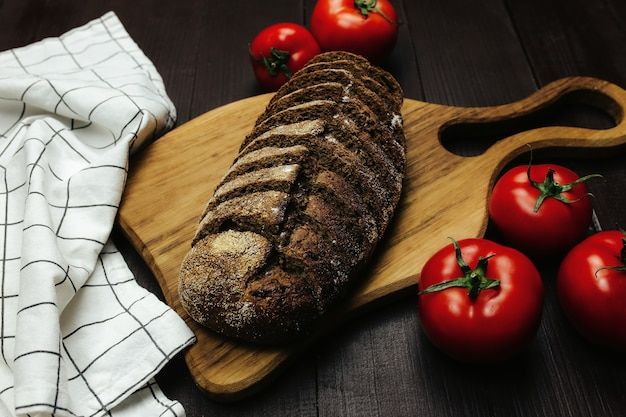 Fresh baked bread and tomatoes on wooden table. high quality photo