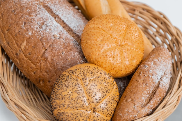 Fresh baked bread in wooden basket on kitchen counter table. Premium Photo