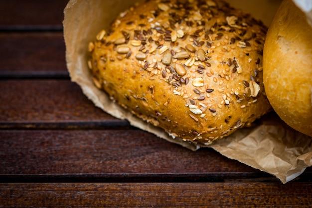 Свежеиспеченный хлеб, завернутый в бумагу, на деревянных фоне.