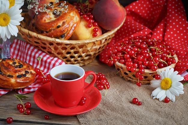 Свежие запеченные булочки с чашкой кофе на деревенском деревянном