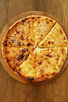木製プレートにハチャプリイメルリ(イメレティアン)と呼ばれる焼きたてのチーズ入りグルジアのフラットブレッド