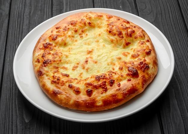 焼きたてのチーズ入りグルジアのフラットブレッドハチャプリイメレティ(イメレティ)を木の板に