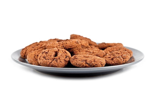 Fresh baked chocolate chip cookies heap on grey plate isolated on white