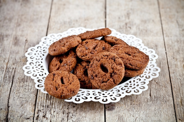 Fresh baked chocolate chip cookies heap on  rustic wooden table