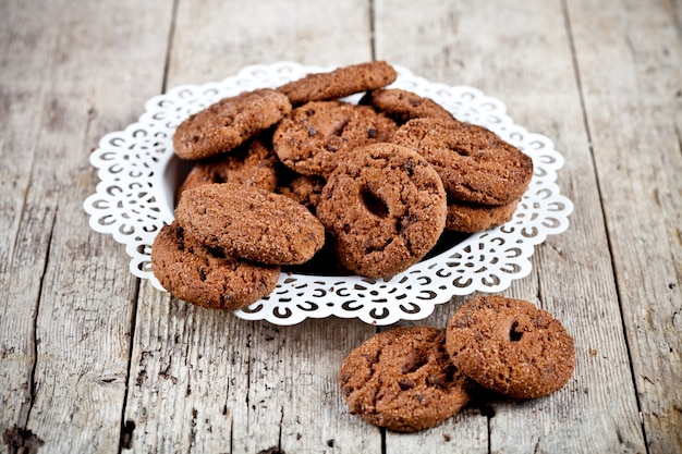Fresh baked chocolate chip cookies heap on white plateon rustic wooden table