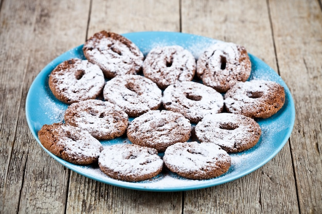 Fresh baked chocolate chip cookies with sugar powder on blue plate on rustic wooden table