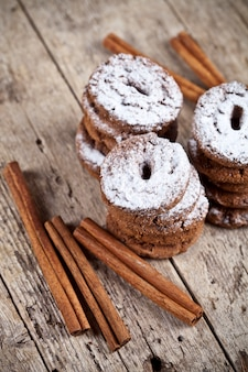 Fresh baked chocolate chip cookies with sugar powder and cinnamon sticks on wooden table