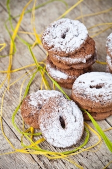 Fresh baked chocolate chip cookies with sugar powder stacks on wooden table