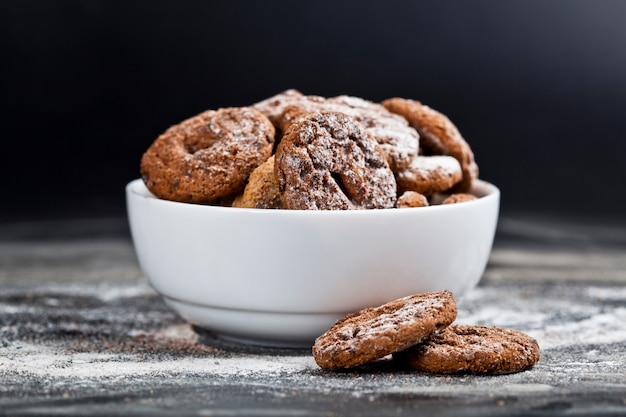 Fresh baked chocolate chip and oat fresh cookies with sugar powder heap in white bowl