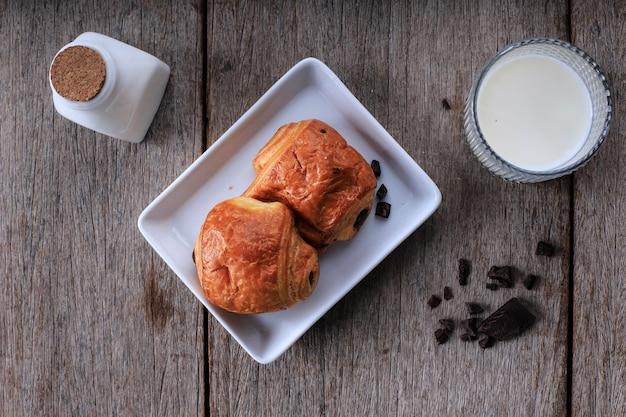 朝食にミルクを添えた焼きたてのチョコレートクロワッサン(pain au chocolat)。テキスト用の素朴なテーブルコピースペースの白いプレートで提供
