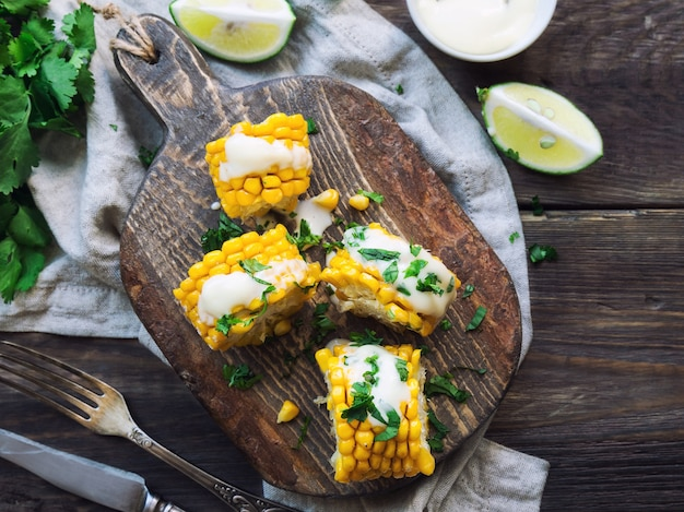 Fresh baked corn cobs with aioli sauce and cilantro on rustic wooden background