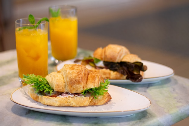 Fresh baked croissant sandwiches with ham and lettuce next to fruit lemonade on marble table