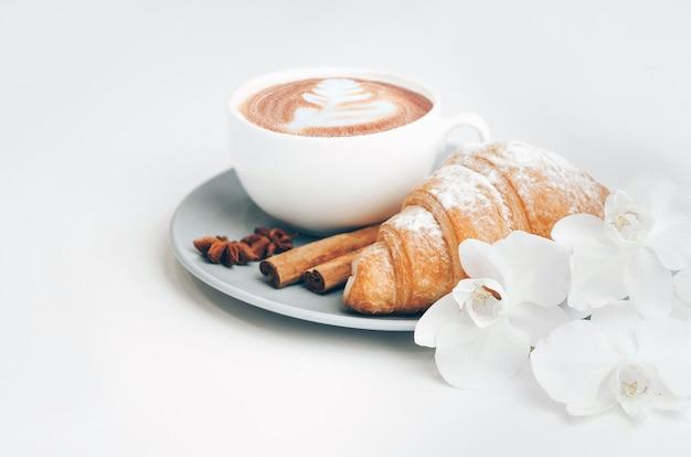 커피 컵과 라떼 아트, 계피를 곁들인 신선한 구운 크로