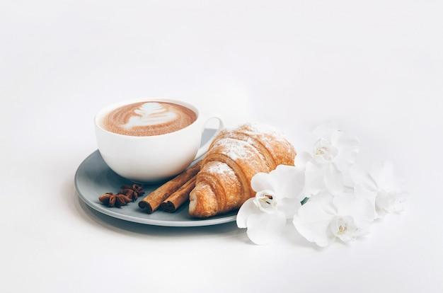 Свежий запеченный круассан с кофейной чашкой, палочками корицы и цветами