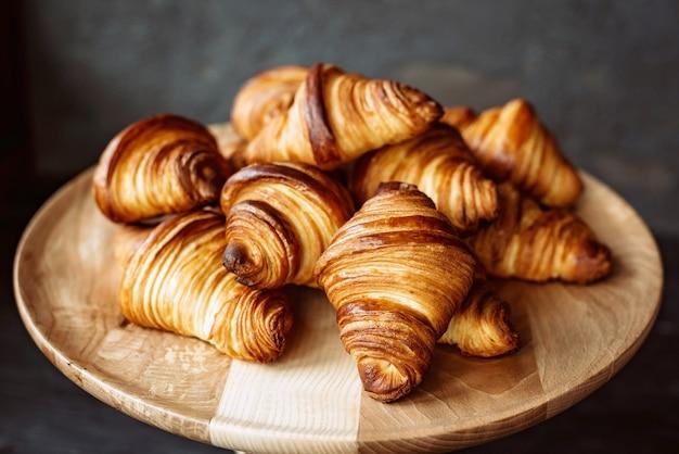 갓 구운 크루아상. 따뜻한 향기로운 버터 크루아상과 롤을 나무 스탠드에 올려 놓으십시오. 프랑스와 미국의 패스트리는 전 세계적으로 인기가 있습니다.