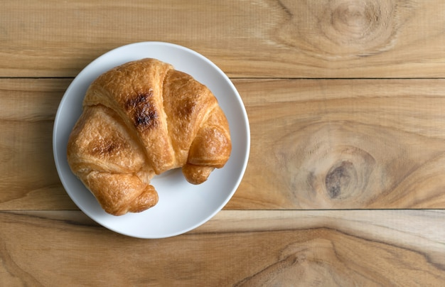Fresh baked croissants on wood table from above